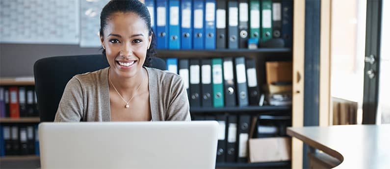 A Cisco Certified Network Professional at her desk. She is looking at the camera and smiling. Get a new career, start your Cisco Certified Network Professional - TSHOOT Certification at CCBST.