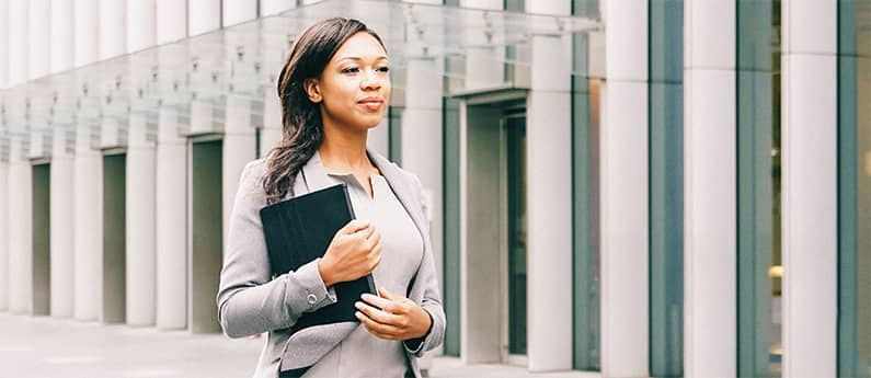 Business woman outside an office, carrying a briefcase. Get a new career, start your Paralegal Diploma Program at CCBST.