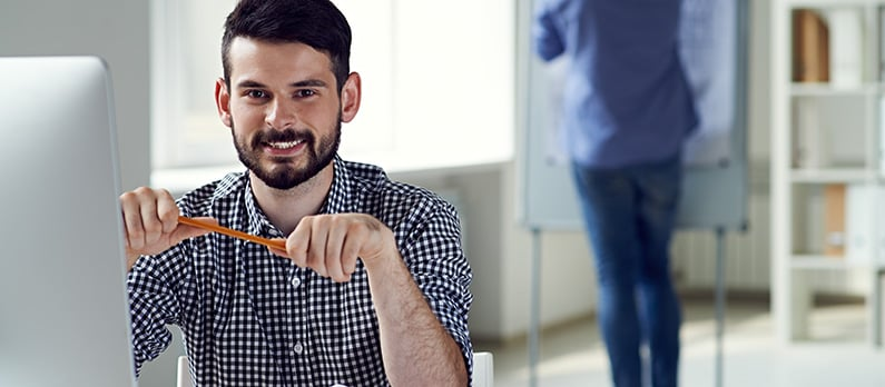 A professional business analyst sitting at his computer, holding a pencil. Get a new career, start your Business Analyst Certificate Course at CCBST.