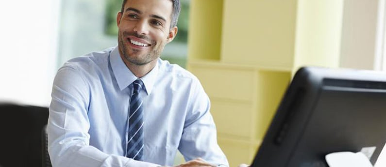 A professional sitting at his desk and smiling. Get a new career, start your Business System Analyst and Project Management Diploma Program at CCBST.
