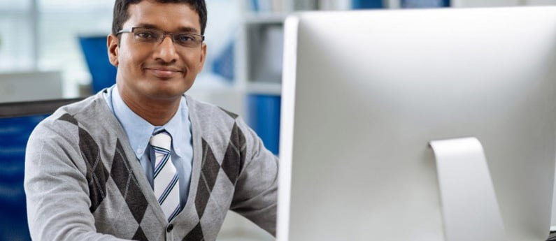A close up of a happy employee in a sweater vest and tie, looking at the camera from his desk. Get a new career, start your CCIE, Routing and Switching Certificate Course at CCBST.