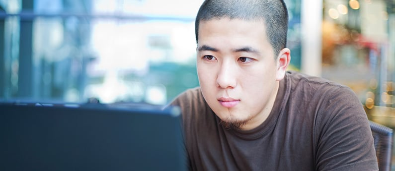 A close up of a dedicated employee working at his computer. Get a new career, start your Cisco Certified Network Associate Certificate Course at CCBST.