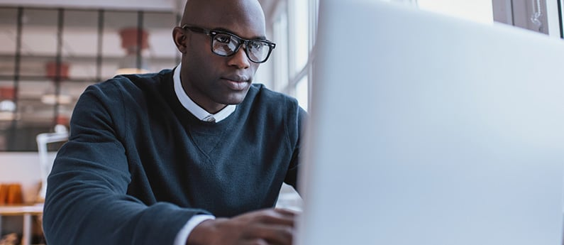 A close up photo of a dedicated employee working at his computer. Get a new career, start your Cisco Certified Network Professional - ROUTE Certificate at CCBST.