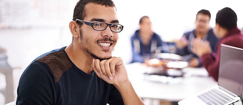 A smiling employee, chin on his hand, sitting with a group of colleagues. He is looking at the camera and smiling. Get a new career, start your Cisco Certified Network Professional - SWITCH Certificate at CCBST.