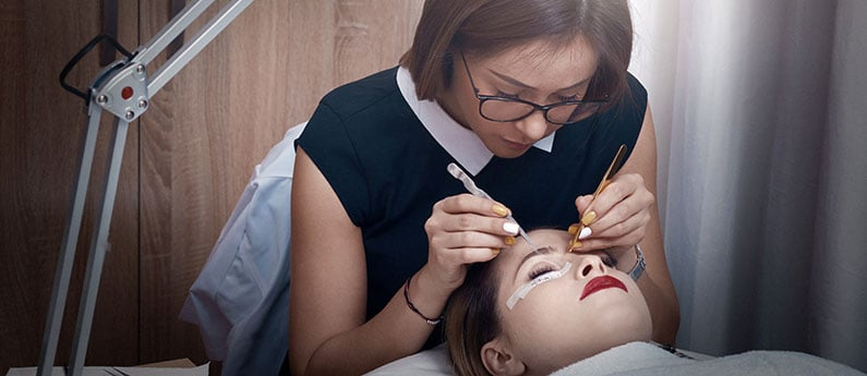 An esthetician working on a client's lashes. Get a new career, start your Classic Lash Extension Certificate Course at CCBST.