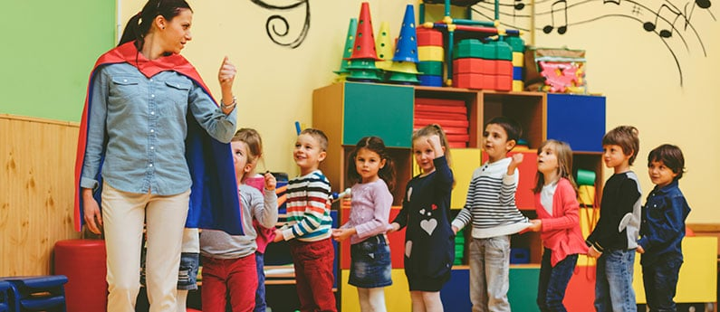An early childcare assistant leading a group of children in play. She is wearing a cape! Get a new career, start your Early Childcare Assistant Diploma Program at CCBST.