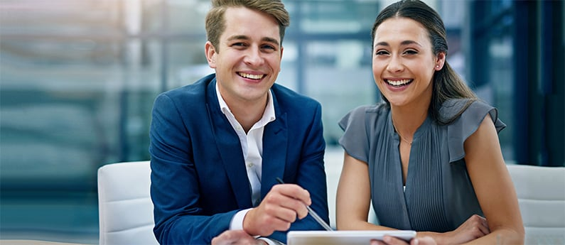 Two professional financial planners sitting at a desk and smiling. Get a new career, start your Financial Planner Diploma Program at CCBST.