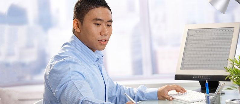 Close up of a Payroll Administrator working at his computer. Get a new career, start your Payroll Administrator Diploma Program at CCBST.