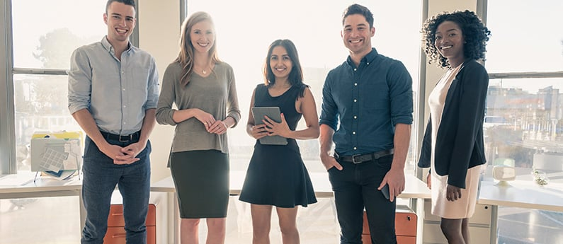 A group of 5 business professionals posing for the camera in an office.