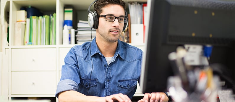 A software professional sitting at his computer, wearing headphones. Get a new career, start your Software Quality Assurance Certificate Course SAQ102 at CCBST.