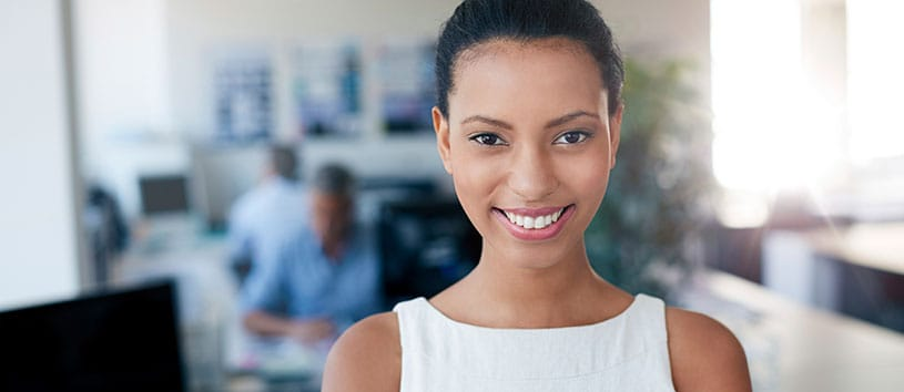 Business woman smiling while in a busy office.