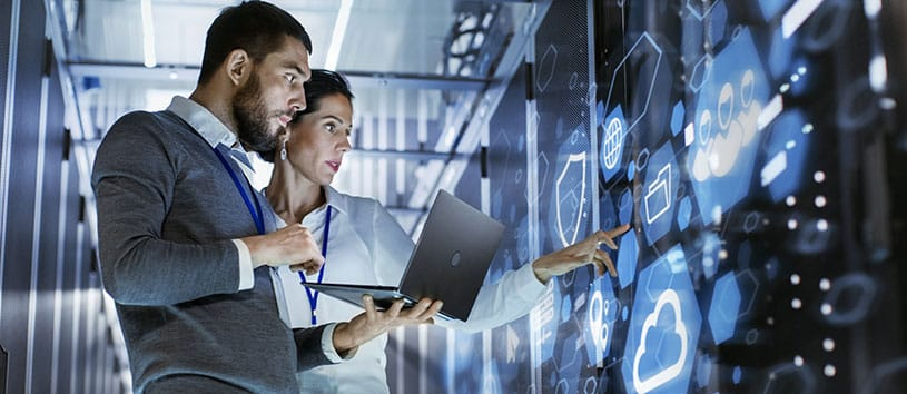 Two IT professionals looking at modern technology displayed on a wall.