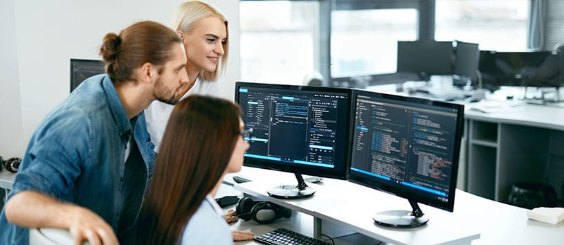 Three employees looking at code on a desktop computer.